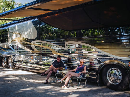 A couple sits outside their large bus-sized RV during Hot August Nights at River West Resort RV and trailer park on West Second Street near downtown Reno.