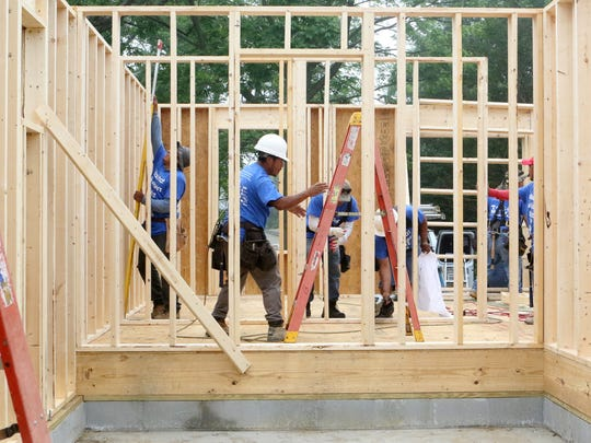 Volunteer builders frame the inside of a new home in