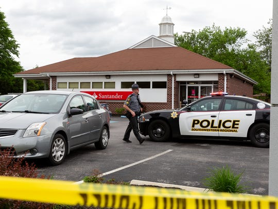 In this photo from Wednesday, the Pennsylvania State Police investigate the shooting outside the Santander Bank on West Hanover Street near North Main Street.