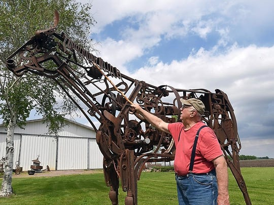 In his May 23, 2018 photo, artist Dick Sonnek, of Mapleton, Minn., talks about his largest work, a horse that stands about 10 feet tall. It took 54 hours to make the creature from old tractor parts and other scrapped equipment.