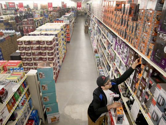 Bi-Mart employee Michael Adam stocks shelves at the new store location on Olney and Mill Hill Drive in Port Orchard on Friday. The store is a membership discount store in Washington, Oregon, and Idaho.