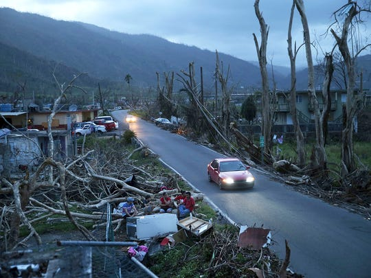 In this Sept. 26, 2017, file photo, neighbors sit on a couch outside their destroyed homes as sun sets in the aftermath of Hurricane Maria, in Yabucoa, Puerto Rico. U.S. government forecasters are expecting an active Atlantic hurricane season. The National Oceanic and Atmospheric Administration forecast released Thursday, May 24, 2018, calls for about 10 to 16 named storms, with about five to nine hurricanes.