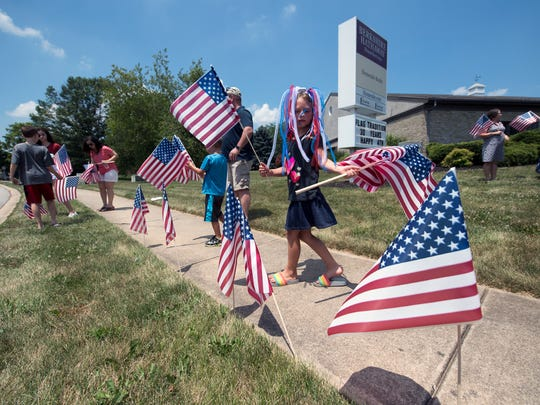 Molly Rager, 7, begins placing flags on Kenneth Road