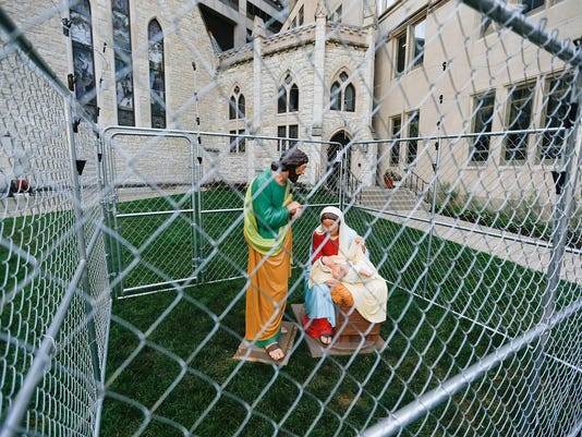 Baby Jesus, Mary and Joseph are locked up in a cage on the lawn of Monument Circle's Christ Church Cathedral