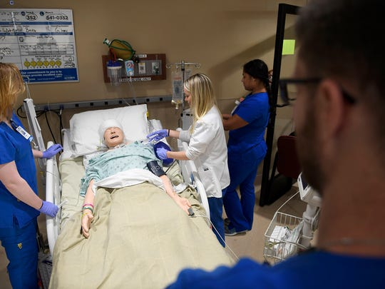 Nursing residents Rubye Fesmire, left, Amanda Terwiilliger, center, and Megan Petty, right, tend to a dummy patient after a lecture at Jackson-Madison County General Hospital on Monday, July 2, 2018.