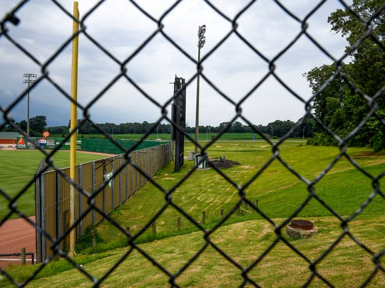 Looking inside the fence towards an open lawn at The Ballpark at Jackson, the future sight of a ten acre dog park in Jackson, Tennessee on Friday, July 6, 2018.