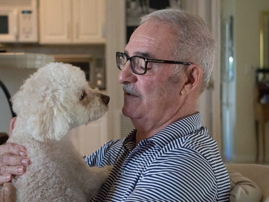 Rich Naccarato holds his puppy, Teddy, in his Naples