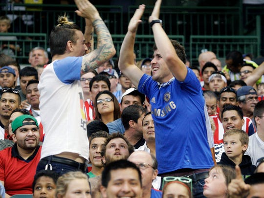 Fans high five in the stands at the first soccer match at Miller Park in 2014.