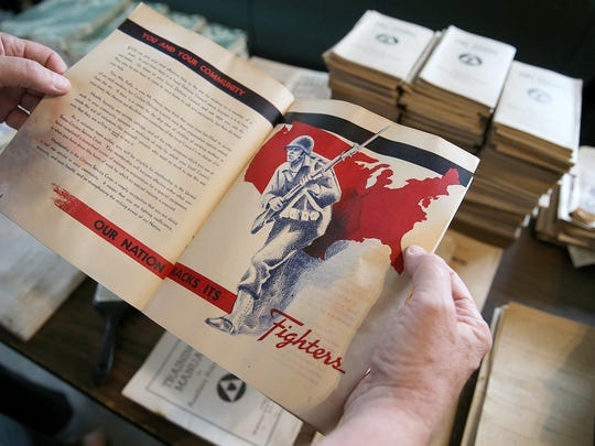 Glenn Stockton looks at a World War II pamphlet he found in his home.