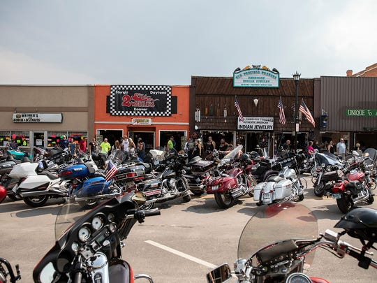 Motorcycles are parked along Main Street during the