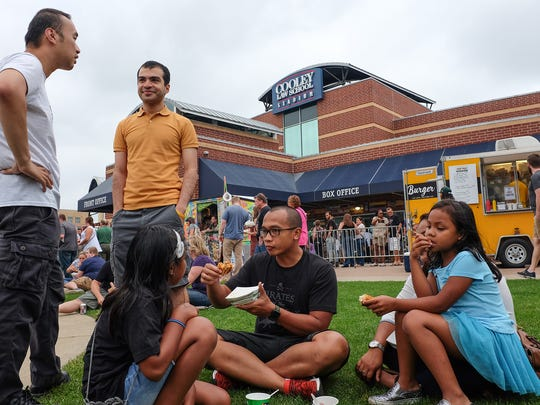 Families try out the food at the Food Truck Mash-Up Saturday, Aug. 25, 2018 at Cooley Law School Stadium.