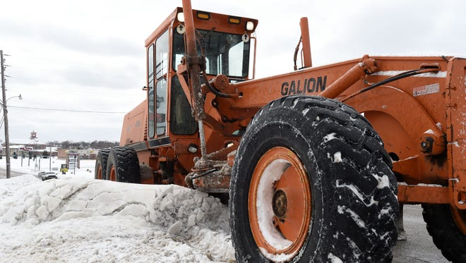 An Arkansas State Highway and Transportation Department road grader clears snow on U.S. Highway 62. Crews were continuing to clear area roadways on Tuesday.