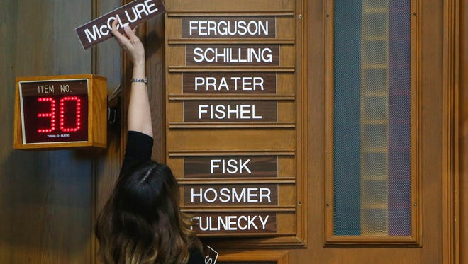 City Clerk Anita Cotter puts Ken McClure's name plate at the top of the board that records the City Council's votes on Tuesday, April 11, 2017.
