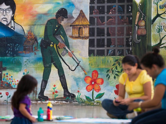 A mural on a wall at a pre-school in San Salvador, El Salvador greet kids and teachers June 19, 2014. The soldier shooting flowers represent killing the beauty of the country. Crime and lack of jobs have sent people from Central America to the U.S. including unaccompanied minors in increasing numbers.