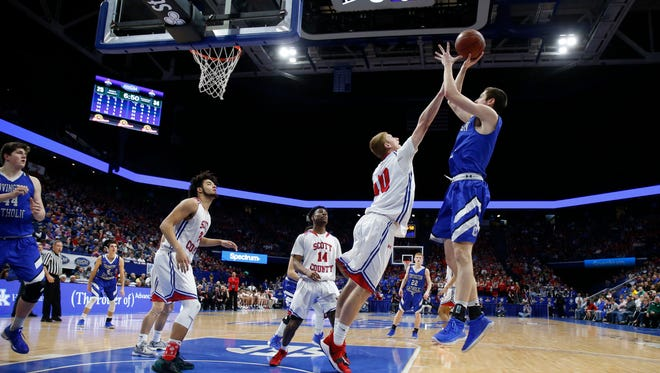 Covington Catholic's C.J. Fredrick, 1, right, puts up a shot against Scott County's Cooper Robb, 10, during the championship game of the Whitaker Bank/KHSAA Boys' Sweet 16 basketball tournament played at Rupp Arena in Lexington, Ky. Sunday March 18, 2018.