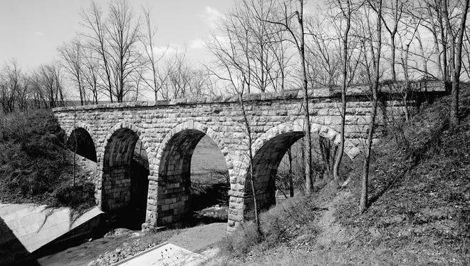 Inmates began construction of the 130-ft long bridge over Folly Mills Creek in early 1873, using granite and rough-hewn squared stone called ashlar. The enormous weight is supported by gently-tapered stone piers.