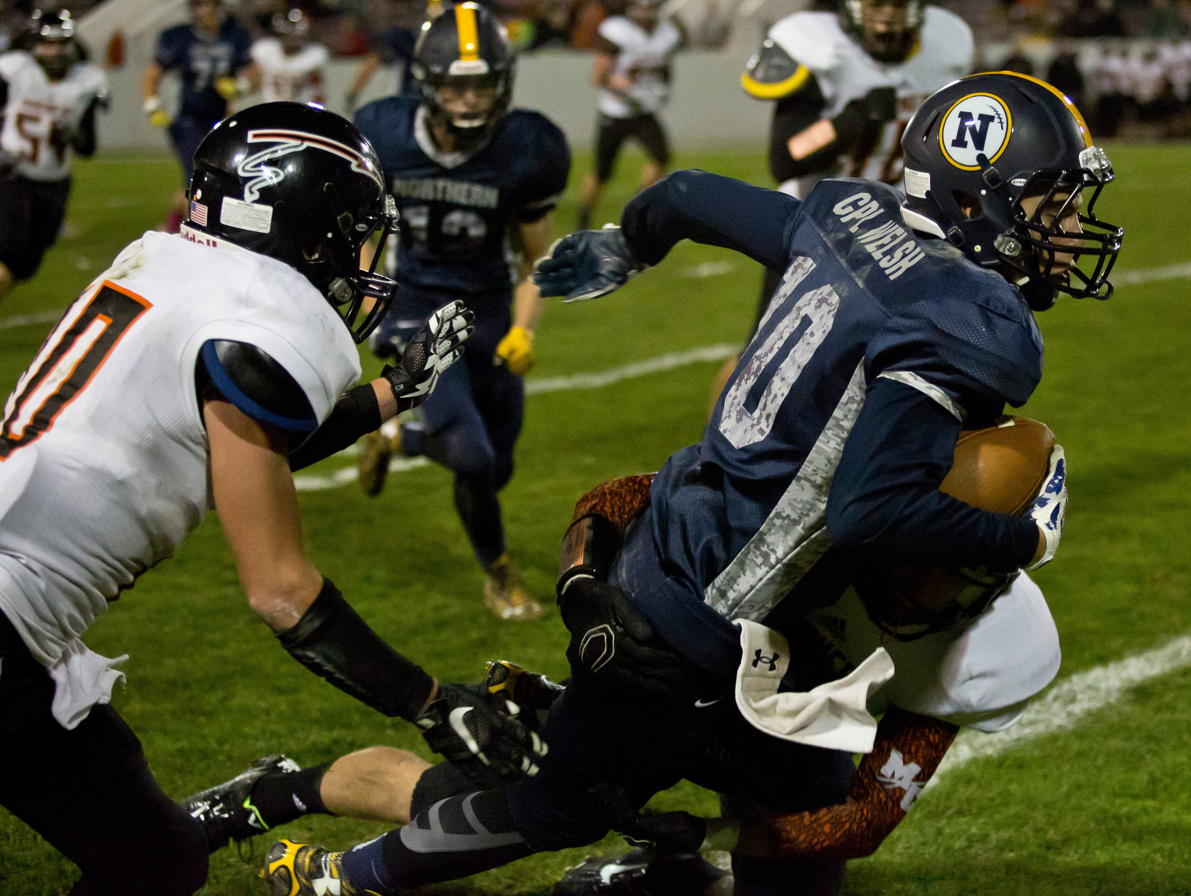 Port Huron Northern senior Geyrd Welsh runs the ball and is brought down by a host of Marine City defenders during a football game Friday, October 9, 2015 at Memorial Stadium in Port Huron.