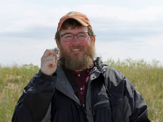 U.S. Fish and Wildlife biologist Vince Cavalieri with a 10-day-old piping plover.