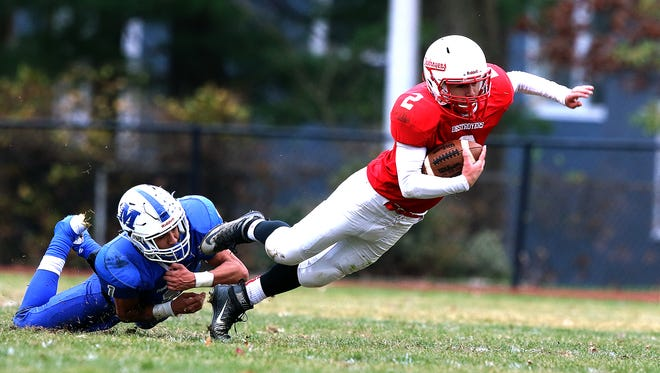 Dunellen's Mike Harmon (2) gets hit by Middlesex's (1) Devin Lanza on Thursday.