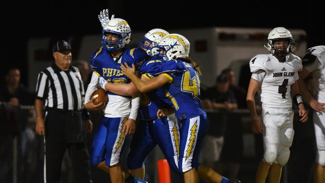 Philo celebrates Isaac Gill's touchdown leap against John Glenn Friday night in Duncan Falls. Gill accounted for all four of the Electrics' touchdowns, including an interception return.