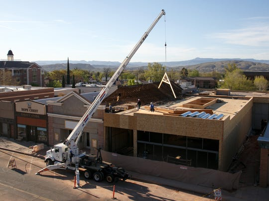Workers use a crane to lift roof trusses into place