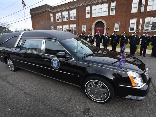 Officers pay their respects as the hearse that carries the body of Newark Deputy Police Chief Robert Sbaraglio proceeds to St. Mary's Church in Nutley on Jan.30, 2017.