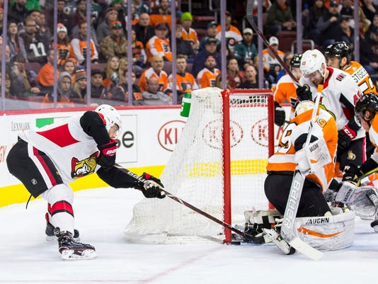 Ottawa Senators' Derick Brassard, left, slips the puck past Philadelphia Flyers' Alex Lyon, right, from behind for a goal during the first period of an NHL hockey game, Saturday, Feb. 3, 2018, in Philadelphia. (AP Photo/Chris Szagola)