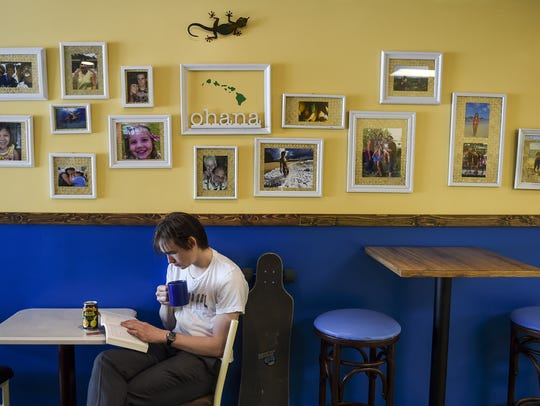 Eric Jones sits and reads inside Aloha Coffee and Grill,
