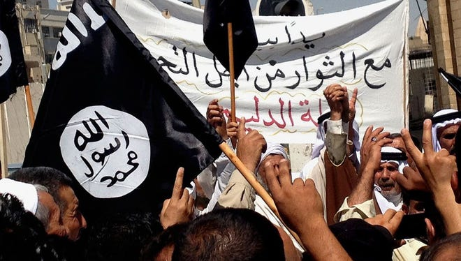 Demonstrators chant pro-al-Qaida-inspired Islamic State of Iraq and the Levant (ISIL) as they wave al-Qaida flags in front of the provincial government headquarters in Mosul, 225 miles (360 kilometers) northwest of Baghdad, Iraq, on June 16, 2014.