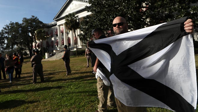 Robert Matthews holds the flag for the League of the South as about 30 members marched to the Capitol sparking counter-protests, numbering more than 100 people on Saturday, Jan. 27, 2018.