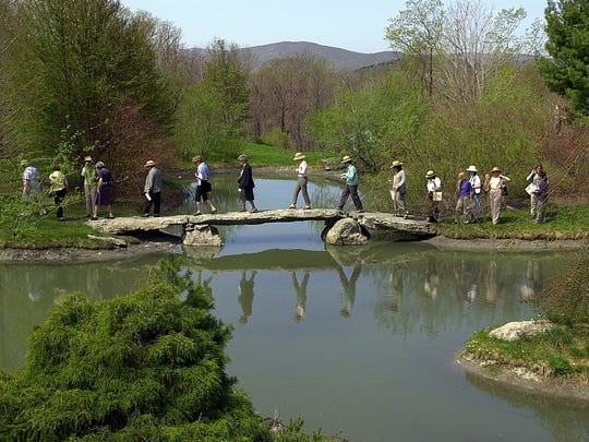 Visitors make their way across the flintstone bridge at Stonecrop Gardens in Cold Spring.