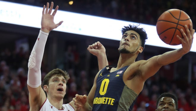 Marquette Golden Eagles guard Markus Howard attempts a basket as Wisconsin Badgers forward Ethan Happ looks on at the Kohl Center.