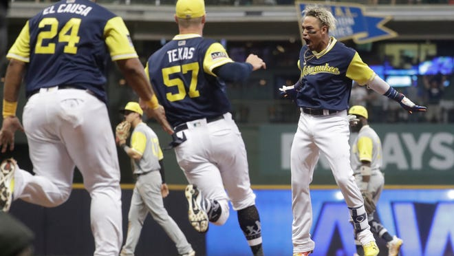 "Milwaukee Brewers' Orlando Arcia celebrates after hitting a walk off single during the 15th inning of a baseball game against the Pittsburgh Pirates Saturday, Aug. 25, 2018, in Milwaukee. The players were wearing ""Players Weekend"" uniforms during the series."