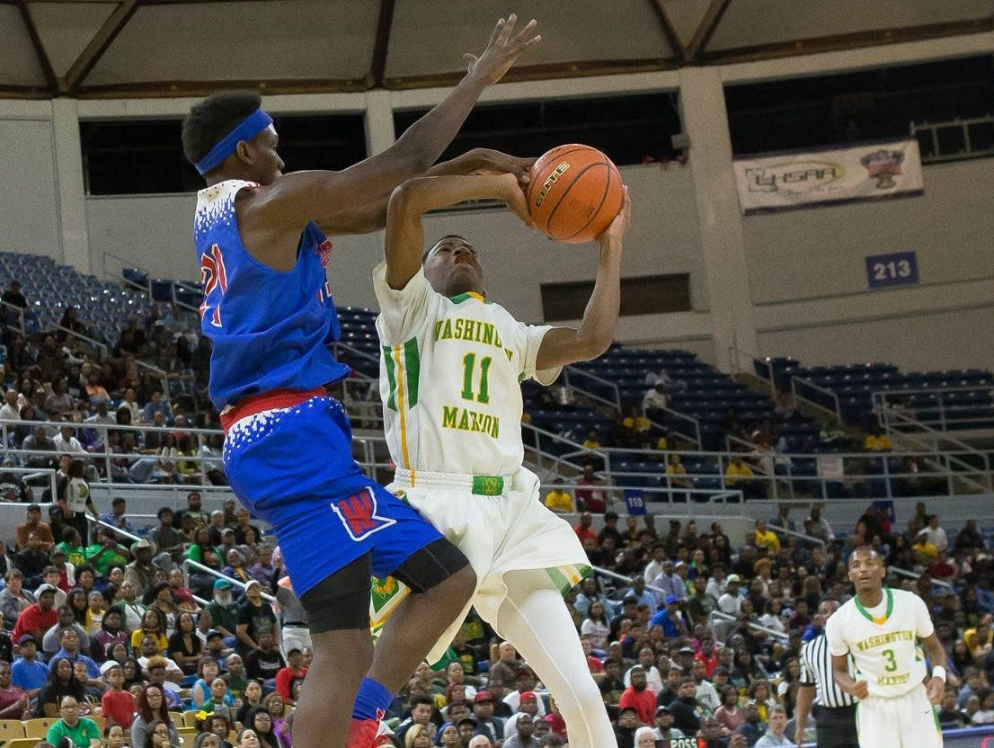Woodlawn's DeVante' Brooks tries to block the shot of Washington-Marion's Cody Stansberry Thursday at Burton Coliseum.