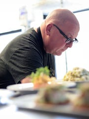 Executive Chef Marc Djozlija plates courses before they are taken to diners on May 26, 2015 at Wright & Company in Detroit.