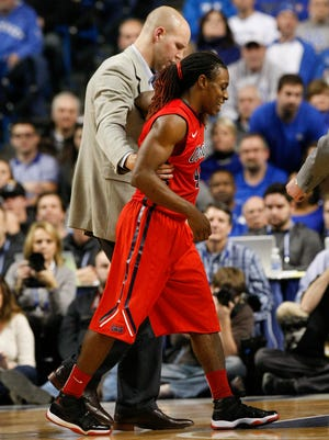 Ole Miss's Stefan Moody, #42, is escorted off the court following an injury during their game against UK at Rupp Arena.  Moody was their high scorer with 25 points, but was unable to finish the game in OT.Jan. 6, 2014