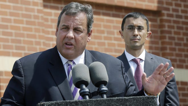In this Aug. 21, 2013 file photo, Gov. Chris Christie answers a question in Camden after naming Paymon Rouhanifard, right, as superintendent of the city's public schools. In 2016, if New Jersey lawmakers approve a measure for the state to takeover Atlantic City, it won't be the first time Trenton wrestled power from local officials.