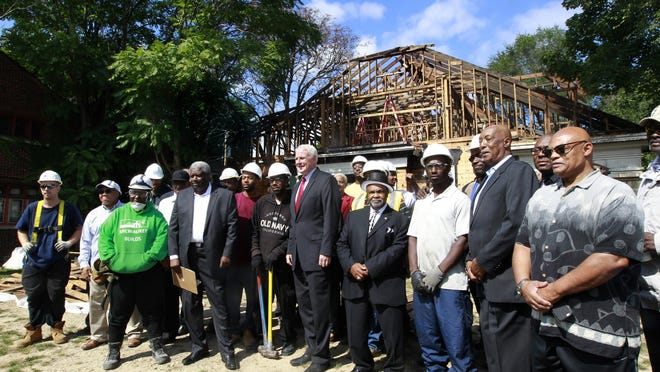 Milwaukee Mayor Tom Barrett (center) stands with A construction crew and community leaders in from of a home at 2709 N. 40th St., in September. Barrett held a press conference to highlight a program that trains workers for jobs in construction trades in the Sherman Park neighborhood.