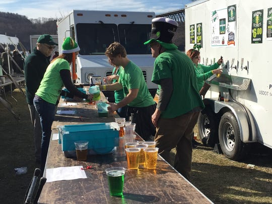 """Volunteers serving on the """"Brew Crew"""" team serve beer during Paddy on the Hudson"""