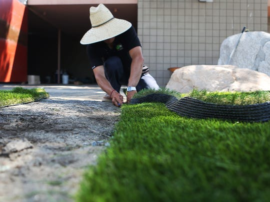 Back Nine Greens foreman Sergio Heras trims the artificial turf to be installed for decorative use in front of a business on Monday in Palm Springs. Turf is becoming more acceptable among desert homeowners.