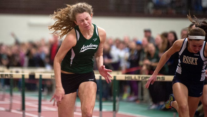 St. Johnsbury's Katherine Cowan, left, lunges at the finish line to win the Division I girls 55 meter hurdles by 0.06 seconds during the Vermont indoor track state championships on Saturday at Norwich University.