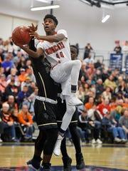 Northeastern's D.J. Hamilton goes for a layup against