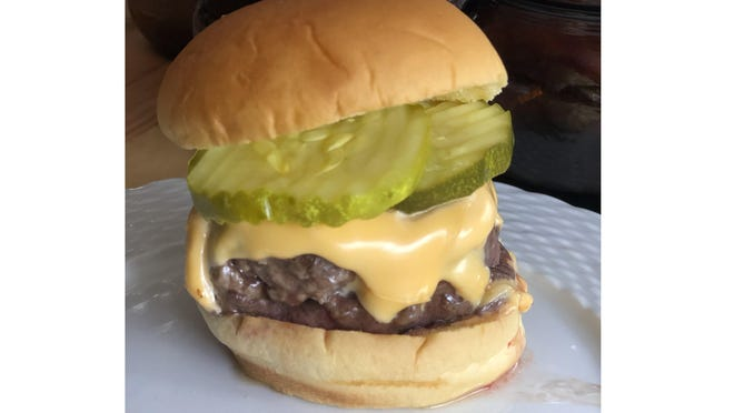 A cheeseburger topped with pickles