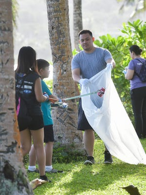 In this Sept. 17, 2016, file photo, volunteers sweep the park and beach areas for rubbish during the International Coastal Clean-Up at the War in the Pacific National Historical Park in Asan.