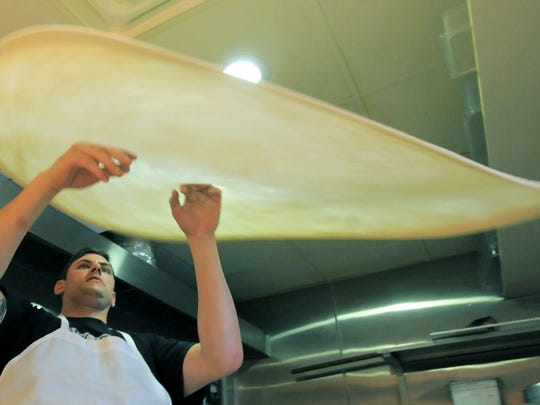 Garrett Marlin stretches a pizza crust at Uncle's Pizzeria while working at the 120 W. Olive St. restaurant in this file photo.