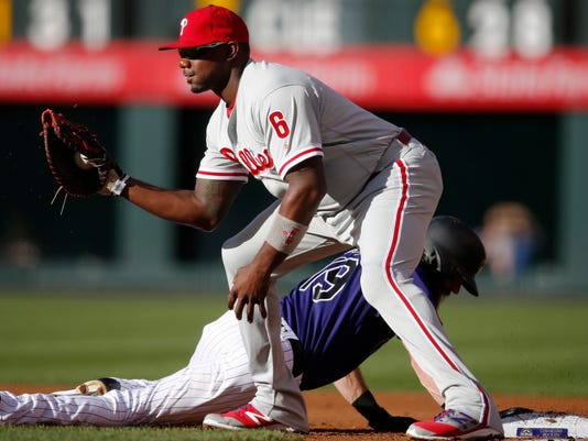 Philadelphia Phillies first baseman Ryan Howard, front, fields the pickoff throw as Colorado Rockies' Charlie Blackmon dives back into first base in the first inning of a baseball game Friday, July 8, 2016, in Denver. (AP Photo/David Zalubowski)