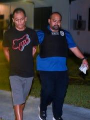 Suspect Jonovan Michael Laitan Cruz, left, is escorted into the Guam Police Department's Hagåtña Precinct, by a Criminal Investigations Division officer, after his arrest on Thursday, April 27, 2017.