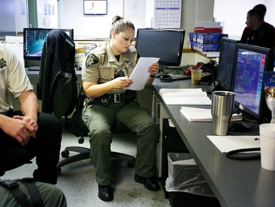 Deputy Melissa Dickson looks at a list of inmates to