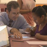 An ASU Prep teacher works with a parent of a student to hone his Spanish verb skills.
