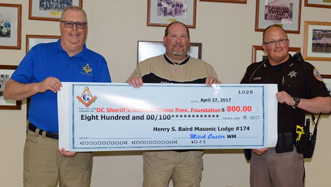 Mitch Custer, left, gives a K9 donation to Sheriff Steven Delarwelle and Deputy Mattassoul.